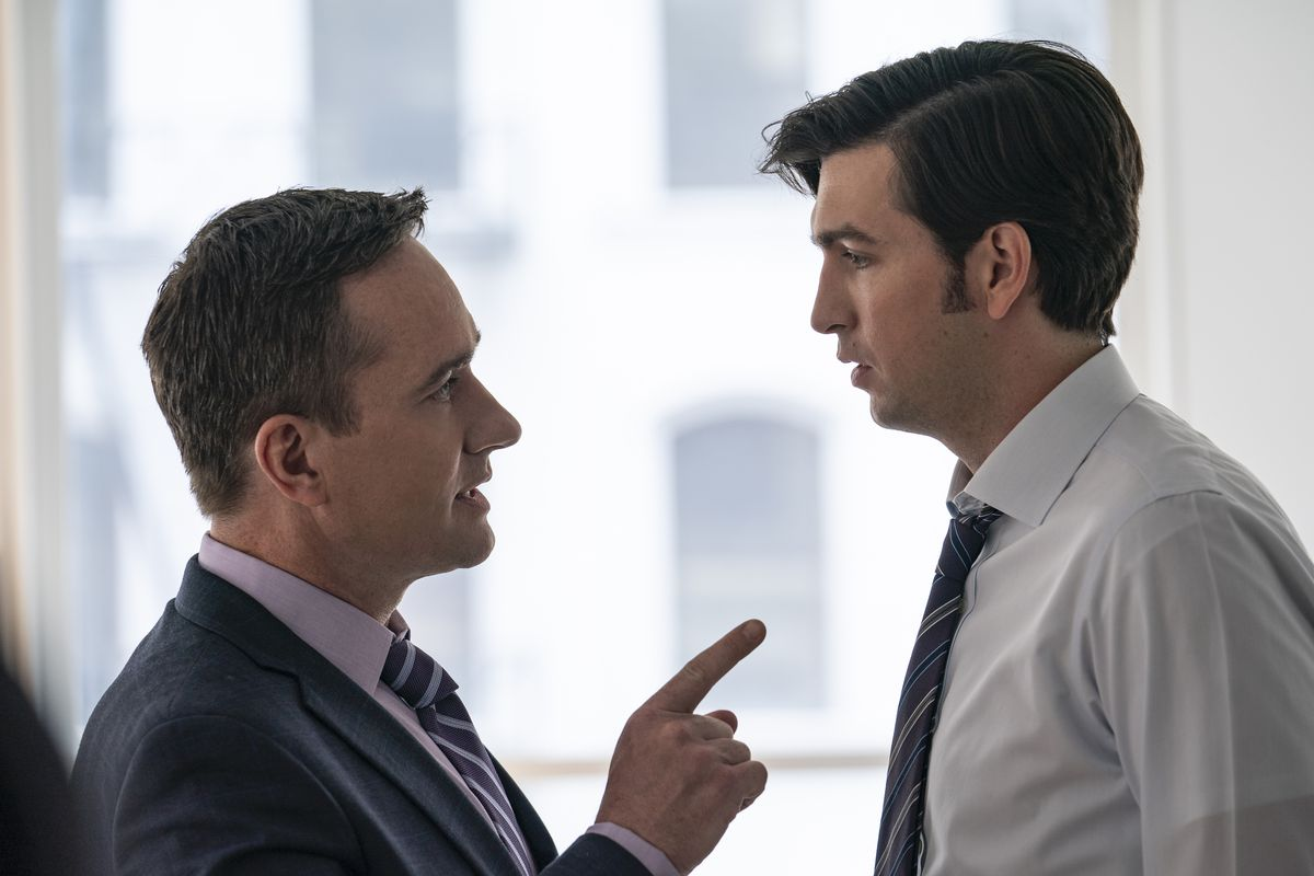 Two men having a conversation while facing each other, the shorter man pointing at the taller.