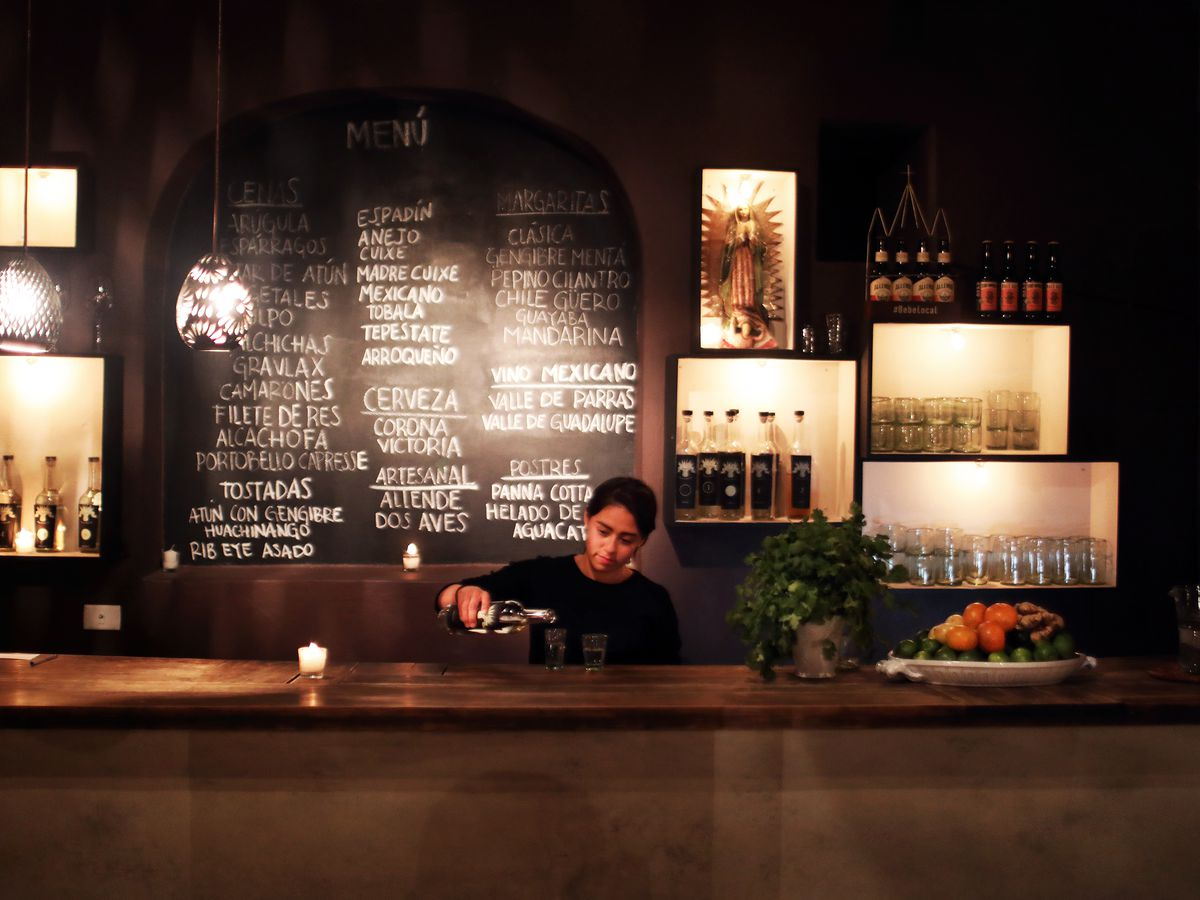 A woman behind a bar pours a drink with a chalkboard menu behind her.