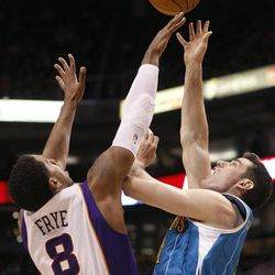 New Orleans Hornets center Jason Smith, right, attempts a field goal over Phoenix Suns forward Channing Frye, left, in the first quarter of an NBA basketball game Sunday, April 1, 2012, in Phoenix.