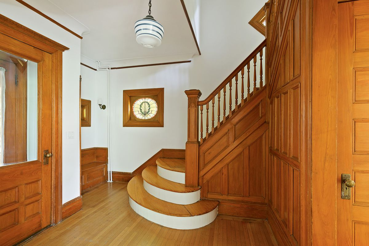A foyer with oak wood details, a staircase, and stained glass windows.