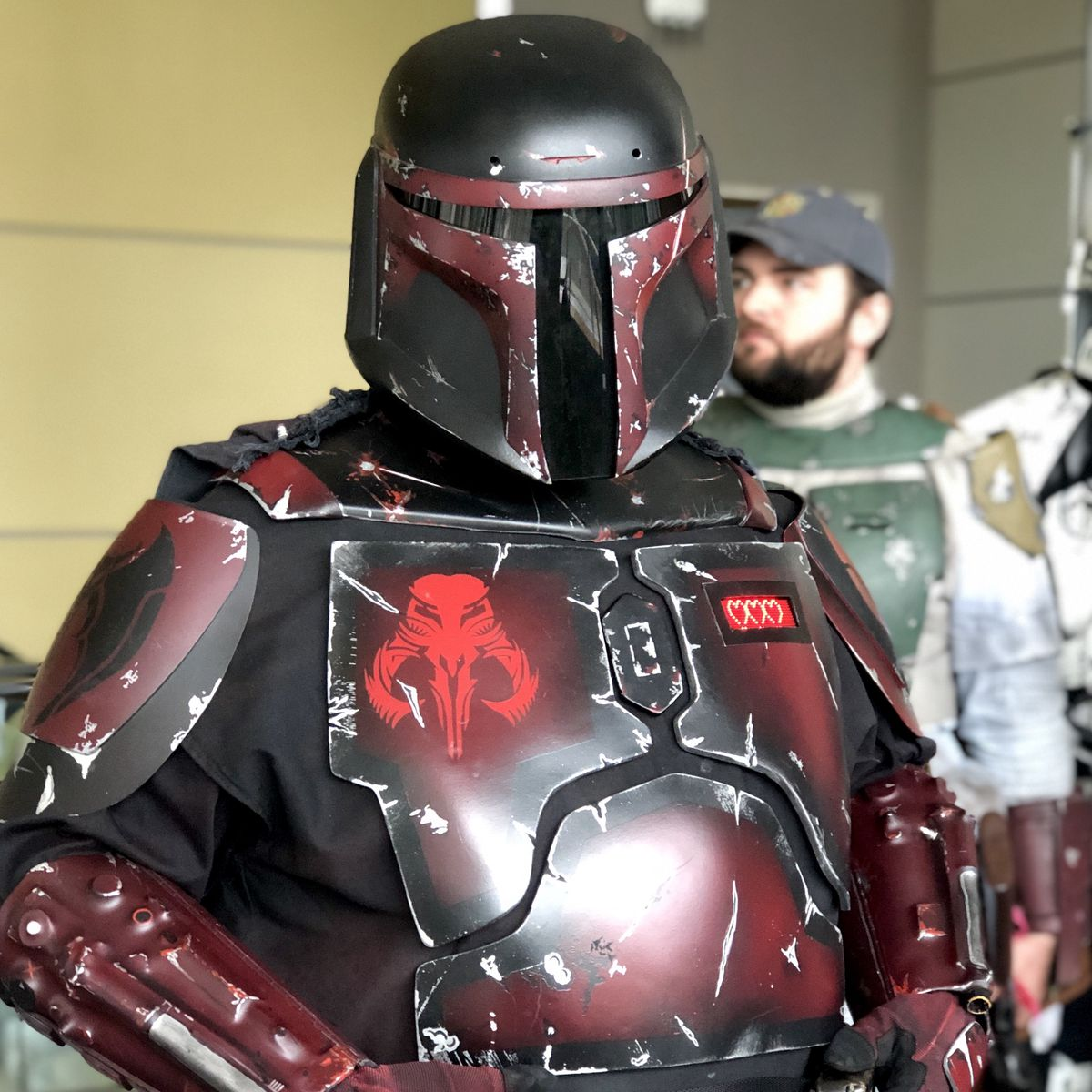 A husky red and black mandalorian armor cosplayer