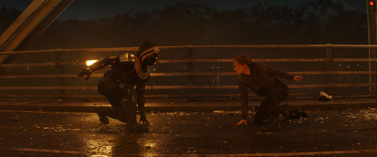 Black Widow faces the taskmaster on a dark bridge in Marvel Studios' Black Widow