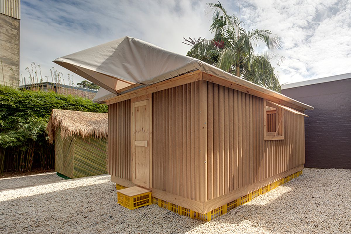 Small, basic structure built from vertical tubes of cardnboard with a fabric roof set upon a platform of plastic cartons, and next to it a similar structure made with green bamboo, sit in a gravel courtyard.