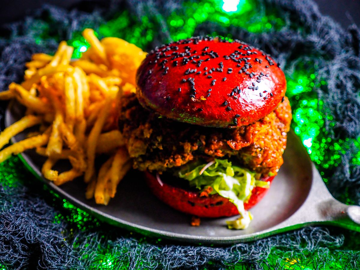 A fried chicken sandwich with a bright red bun