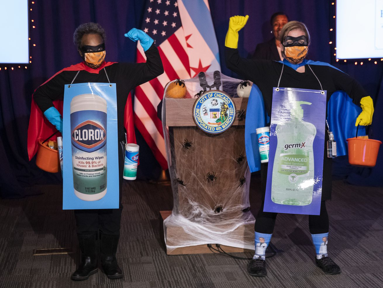 """Mayor Lori Lightfoot and Dr. Allison Arwady, commissioner of the Chicago Department of Public Health, wear """"Rona Destroyer"""" costumes and pose for a photo at City Hall"""
