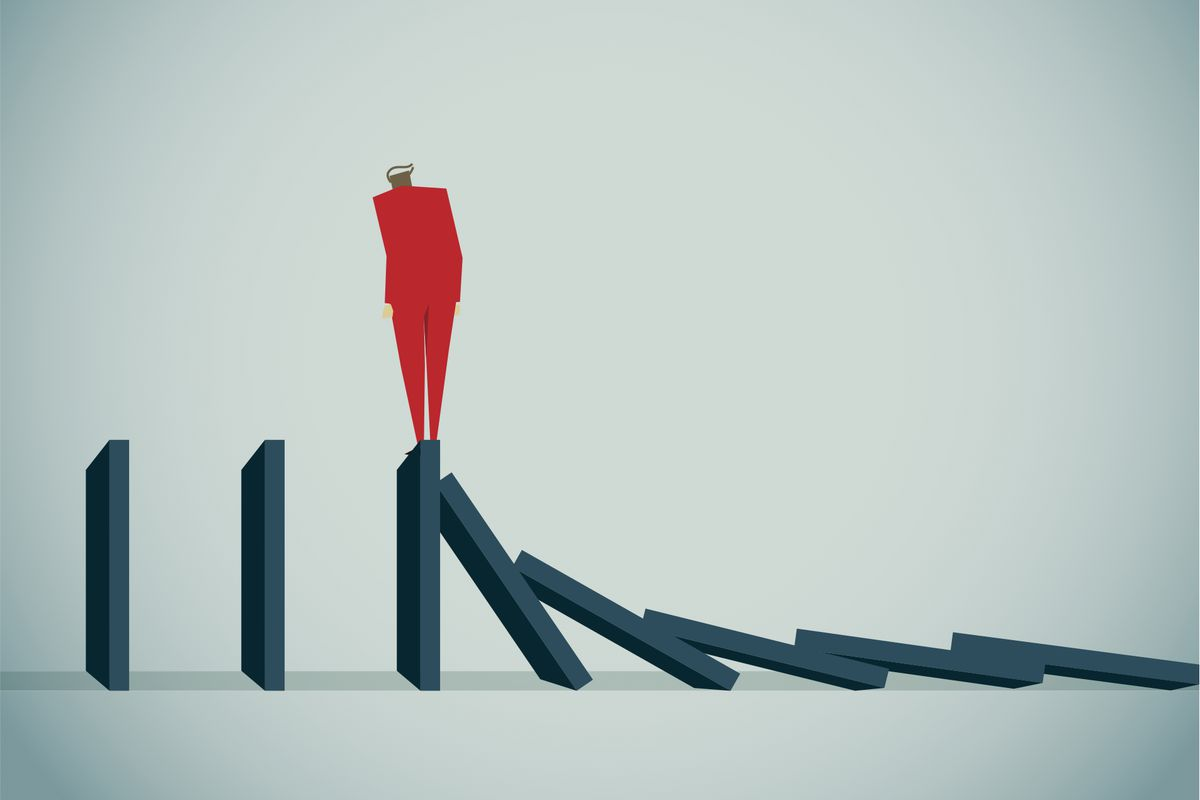 An illustration depicts a person standing on the edge of dominoes.