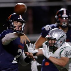 Brighton quarterback Jack Johnson passes the ball just ahead of getting hit by Olympus' Isaac Wirthlin as they play a high school football game at Brighton in Cottonwood Heights on Friday, Sept. 10, 2021. Olympus won 35-28.