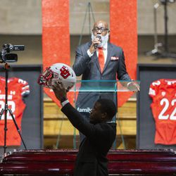 An officiant holds up Aaron Lowe's football helmet in his honor during a funeral service at Family Cathedral of Praise on Monday, Oct. 11, 2021, in Mesquite, Texas. Lowe, a student and football player at the University of Utah, was was shot and killed on Sept. 26 at a postgame party.