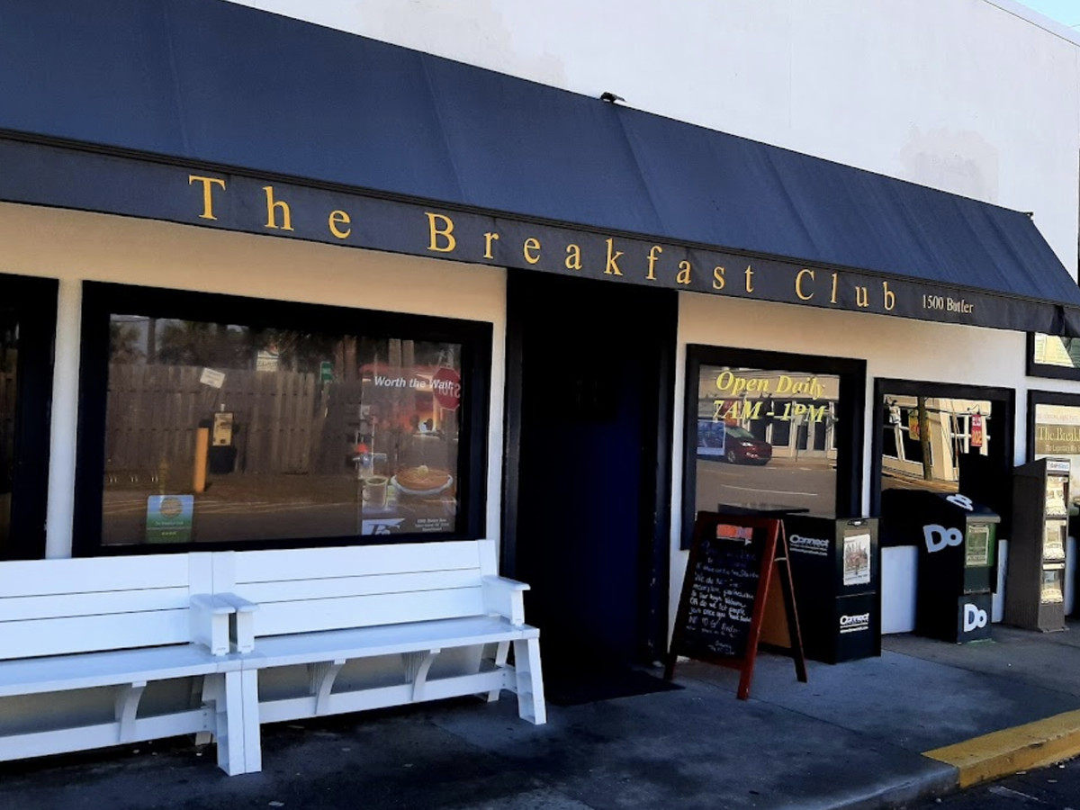 The outside of the Breakfast Club restaurant, which includes white benches for waiting when the spot gets full on weekends and during breakfast on Tybee Island, GA.
