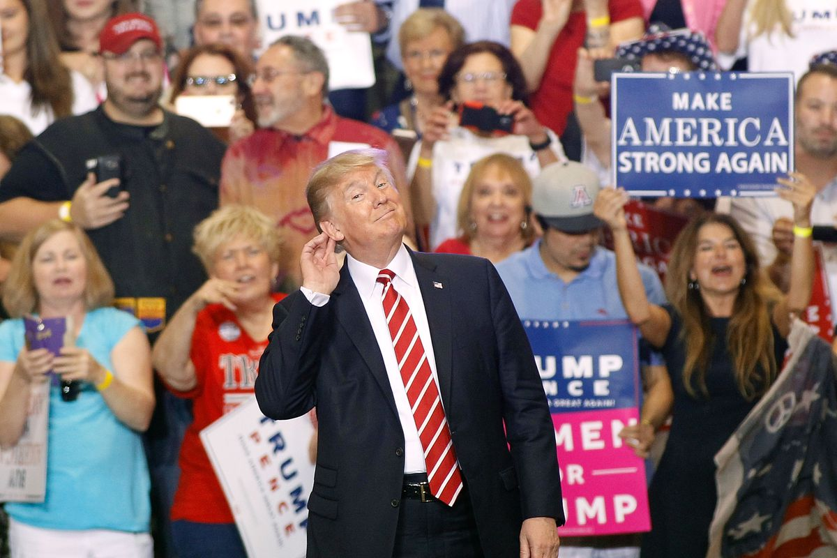"""President Trump at a political rally in Phoenix holds his hand to his ear as though saying, """"I can't hear you."""""""
