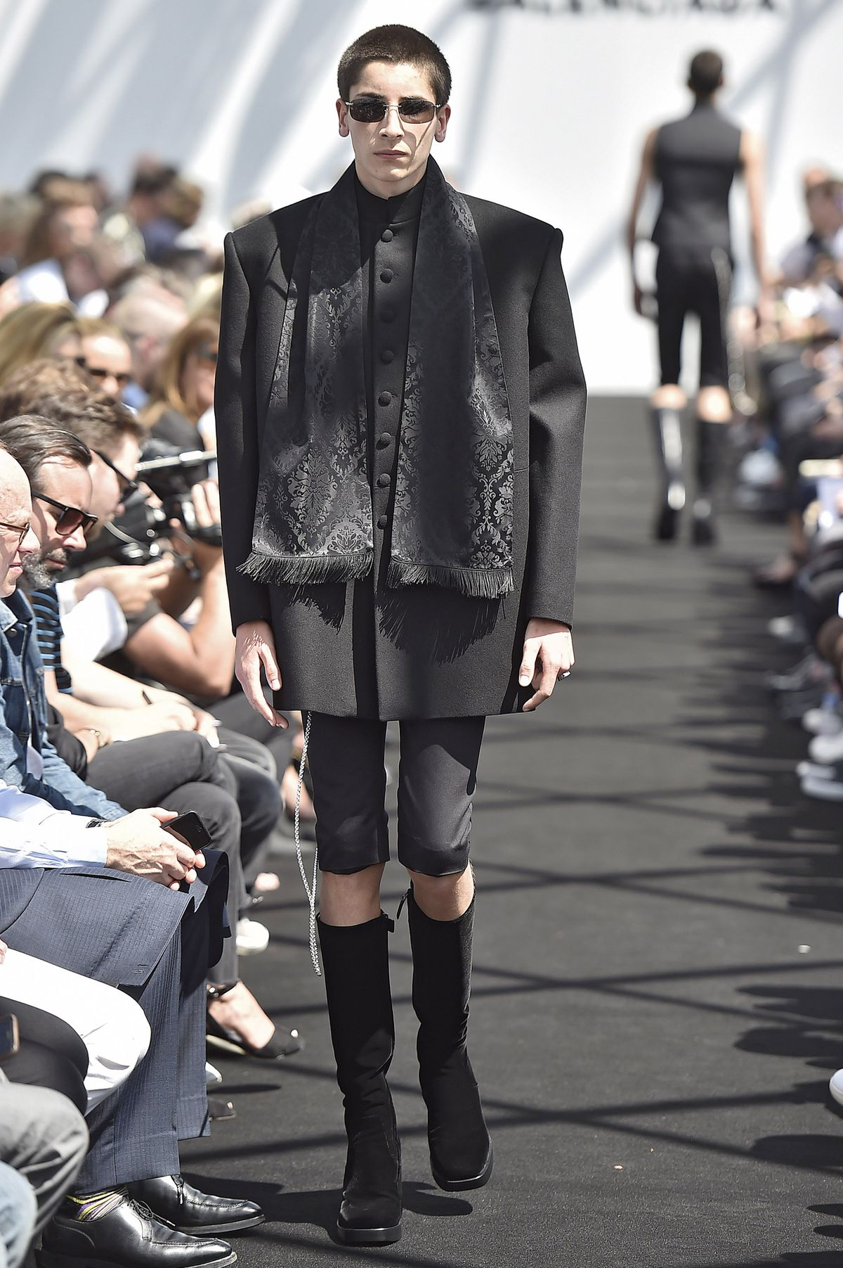 A model walks the runway at Balenciaga's spring 2017 menswear show wearing an oversize jacket and super-skinny black pants.