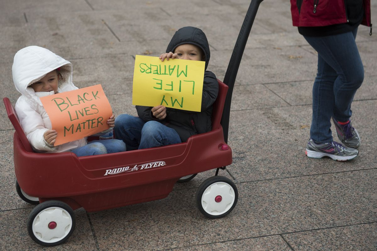 Two young children hold signs during a demonstration by the group Black Youth Project 100 stage a 'lie-in' near the City Council offices in Washington, DC, November 25, 2014.