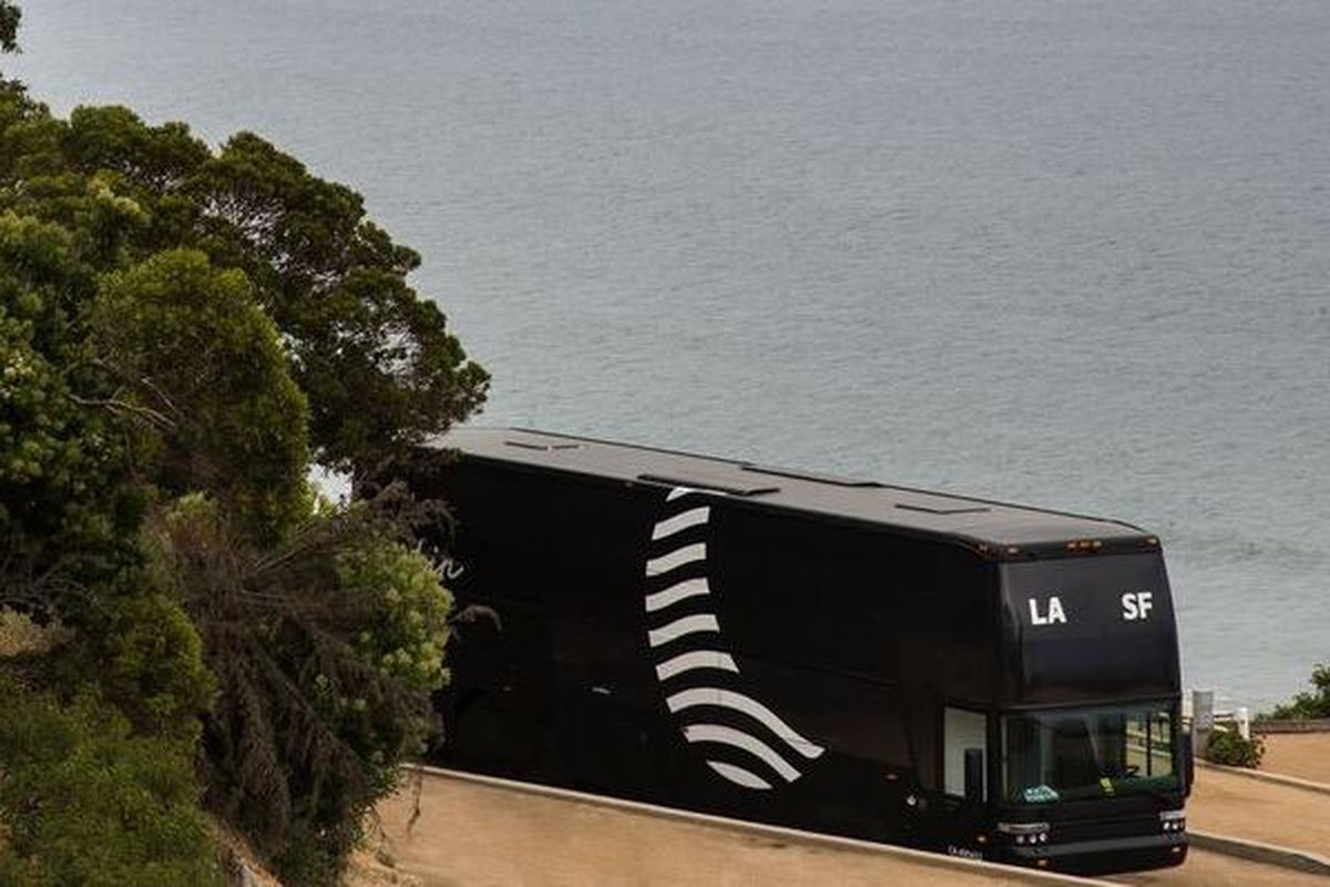 A black and white bus driving along the California coast with ocean in the background.