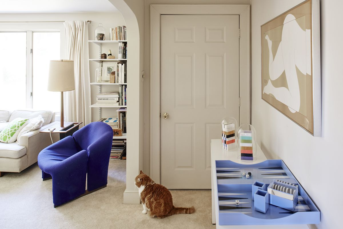 A large orange and white cat sits in front of a white door. On one wall in the foreground is a hanging framed work of art above a table. On a wall in the distance is a large window and a bookcase full of books. There is a blue chair and white couch in the