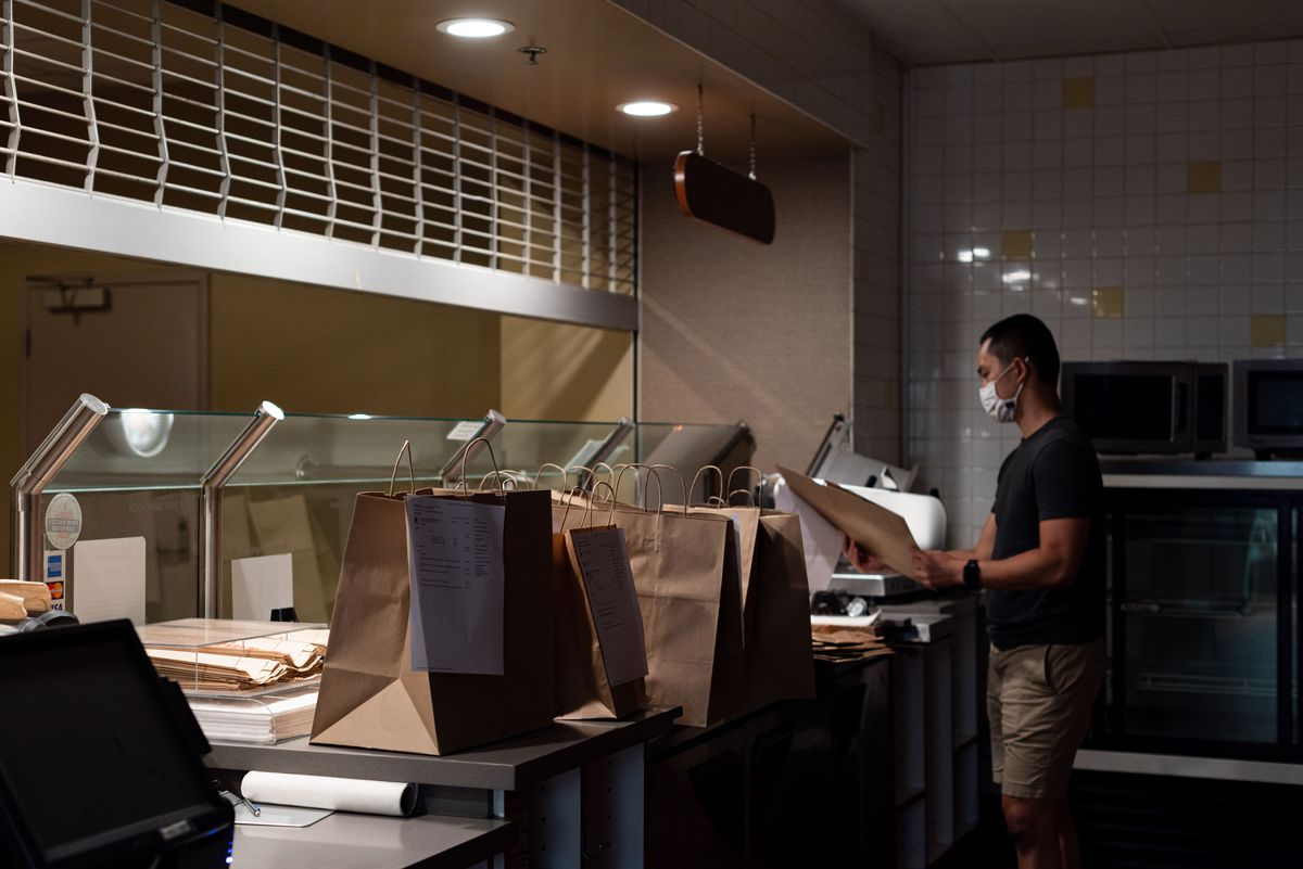 As light dims inside of a half-closed restaurant, a worker bags to-go orders.