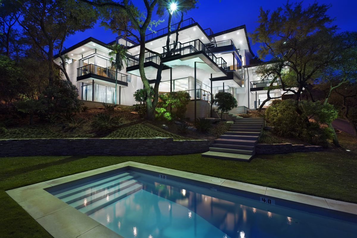 Night shot of several-level modern home on a hill, lighted from inside, all windows, pool in foreground
