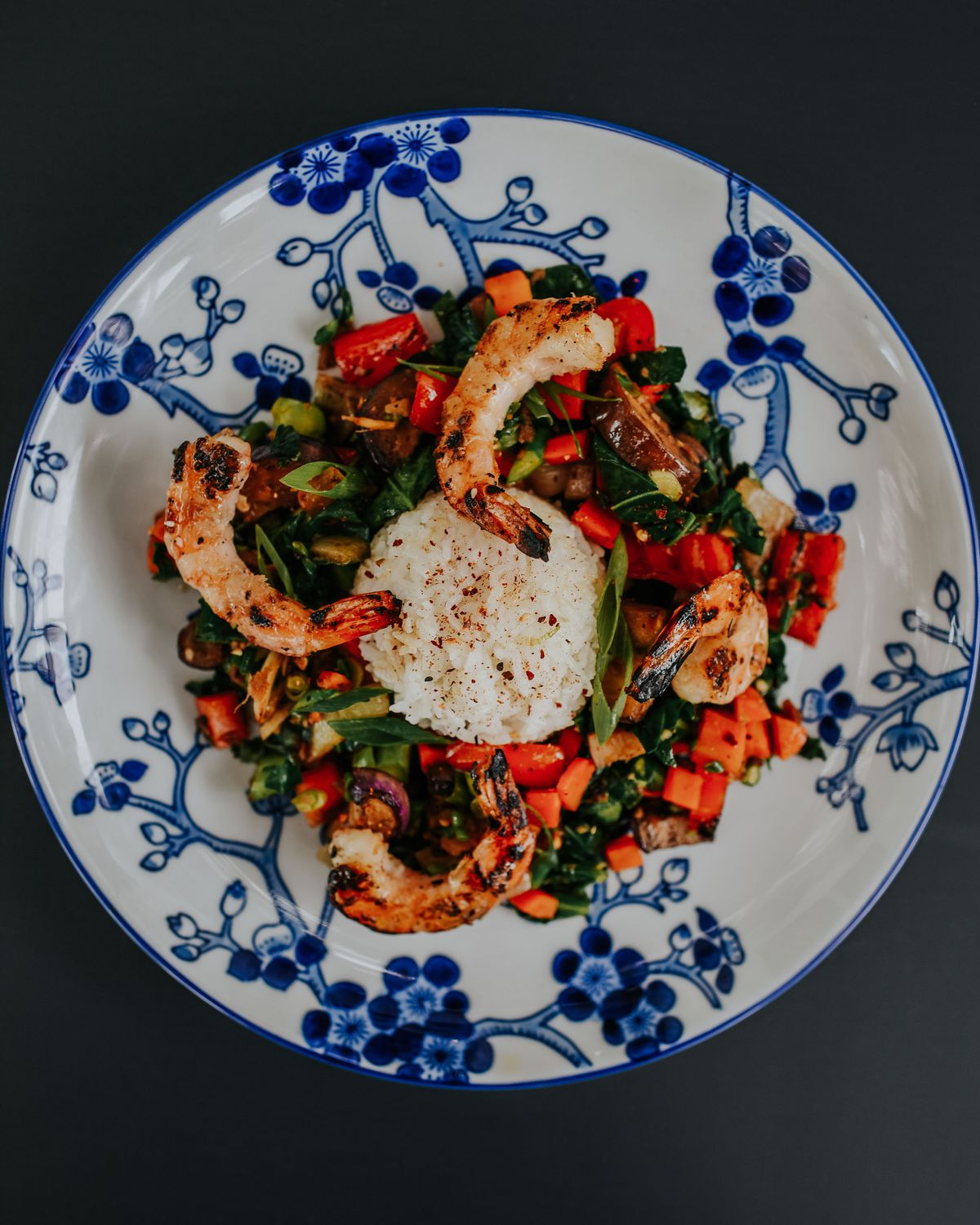 A blue and white Chinese floral patterned plate with Imperial shrimp stir-fry and neat dollop of white rice in the center from Mow's Chinese Kitchen in Alpharetta, GA