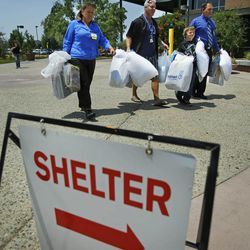 From left, Tara Reyes, Pastor Tim Parker, Markis Youoston and Kevin Ray carry donate supplies from Wal-Mart to the Red Cross Shelter, Monday, July 1 2013 in Prescott,  Ariz. (AP Photo/The Arizona Republic, David Kadlubowski)