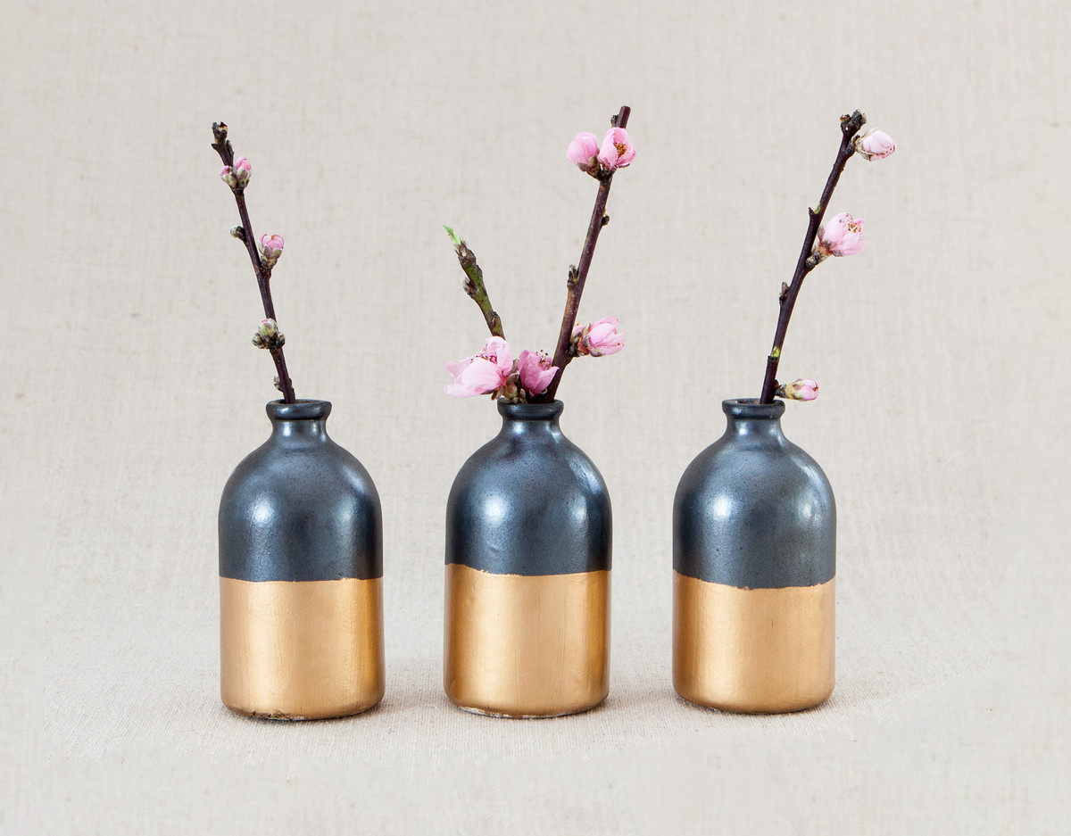 Three vases sit in a row against a neutral background. Each vase is dark gray with a gold base. There are stems with pink flower buds in each vase.