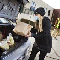 Monet Palmer places food into a trunk at a Crossroads Urban Center food distribution event at Rowland Hall in Salt Lake City on Wednesday, Dec. 23, 2020. This year's Christmas food distribution marks the 23rd year of collaboration with Rowland Hall. Crossroads has been providing social services to individuals and families in need in Salt Lake City and the surrounding areas for over 50 years. Funding and support for the Christmas food distribution came from the staff, students and families of Rowland Hall, the Utah Food Bank, the Eccles Broadcast Center at the University of Utah, the B.W. Bastian Foundation, Rocky Mountain Power, and dozens of other individuals and local religious congregations.