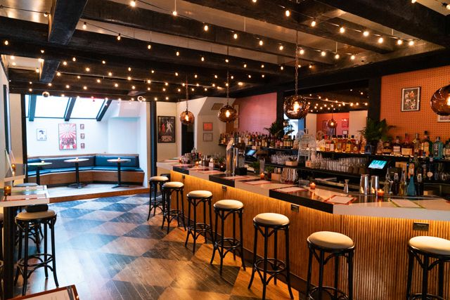 Katana Kitten has a bar to the right with stools and lights hanging above