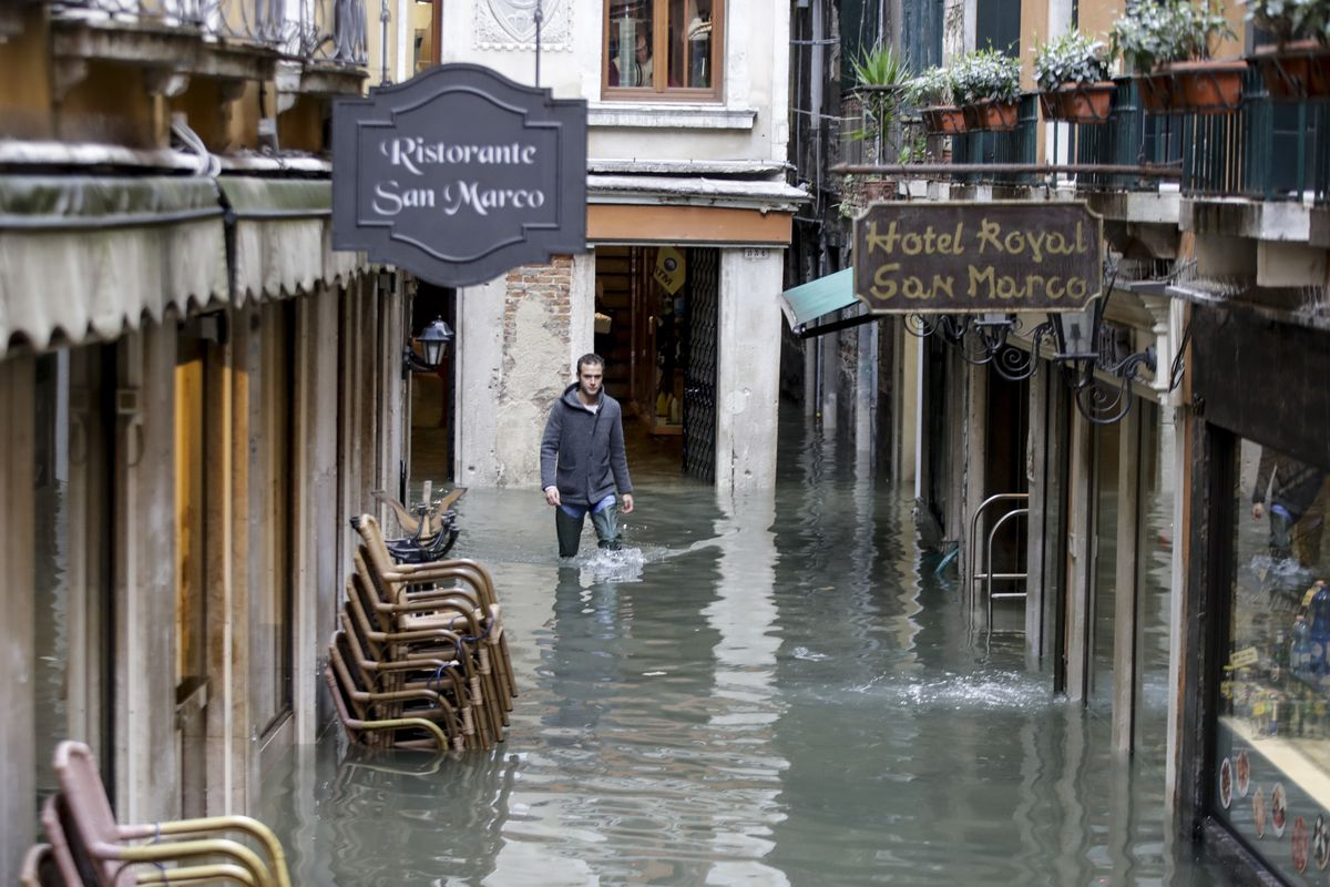 A man makes his way through the flooded streets of Venice, Italy.