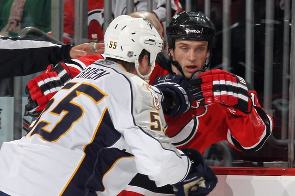 Shane O'Brien (55) of the Nashville Predators hits Tim Sestito (14) of the New Jersey Devils at the Prudential Center on December 17 2010 in Newark New Jersey.  The Predators defeated the Devils 3-1. (Photo by Bruce Bennett/Getty Images)