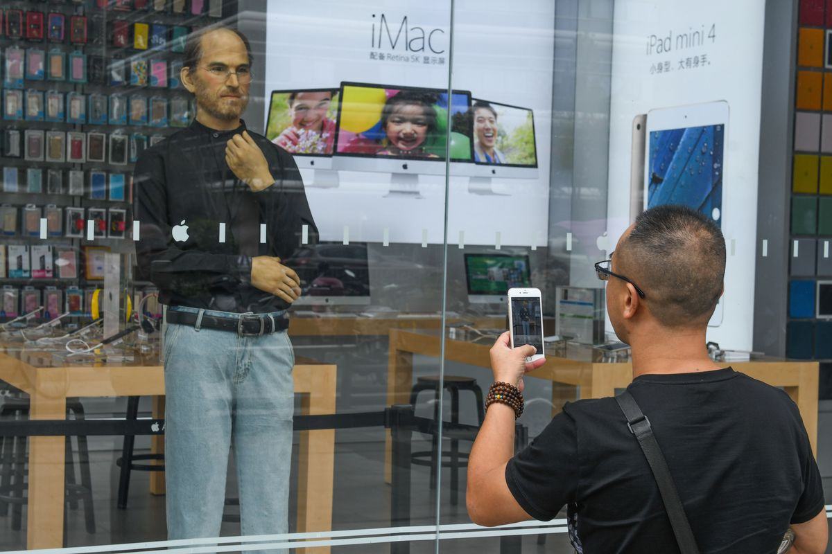 A life-size silicone sculpture of Apple CEO Steve Jobs is seen in an Apple Store display window in China.