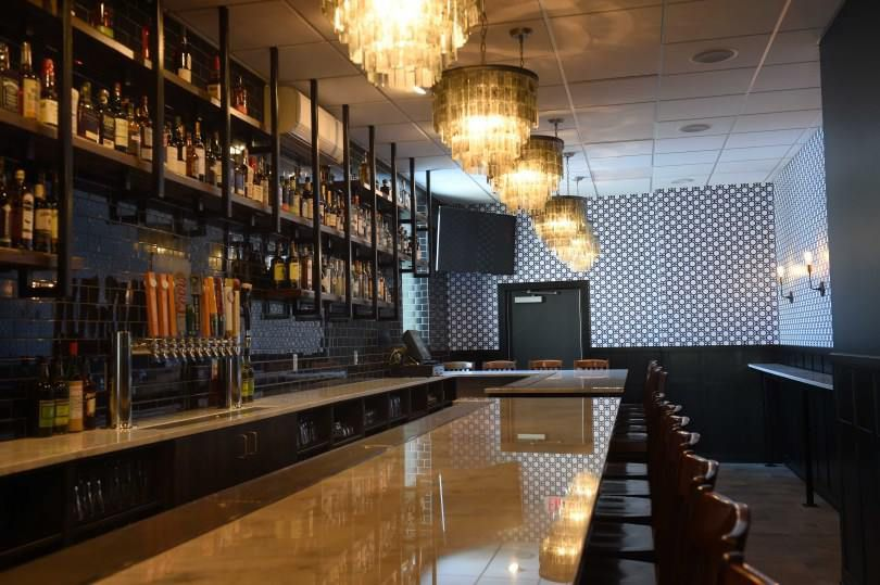 A long, lean bar with chandeliers above and a high, black painted bar
