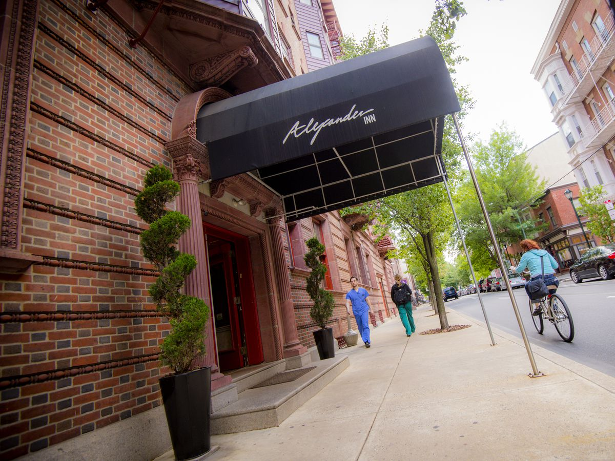 The exterior of the Alexander Inn in Philadelphia. There is a black awning and the facade is red brick.