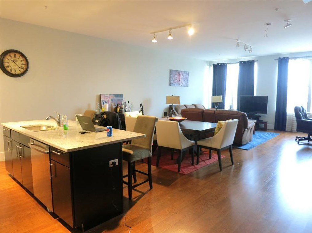A large, open living room-dining room-kitchen area with furniture.