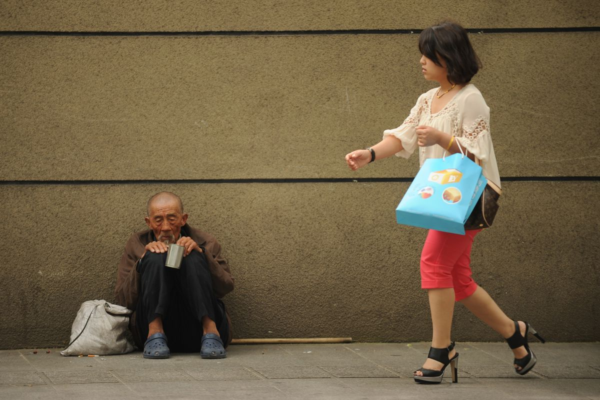 A woman walks by a man begging in Shanghai in 2012.