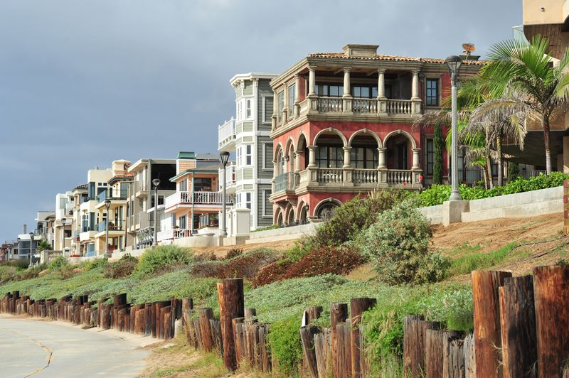 Large homes in a variety of architectural styles, from colonial to Mediterranean, line a beachfront.