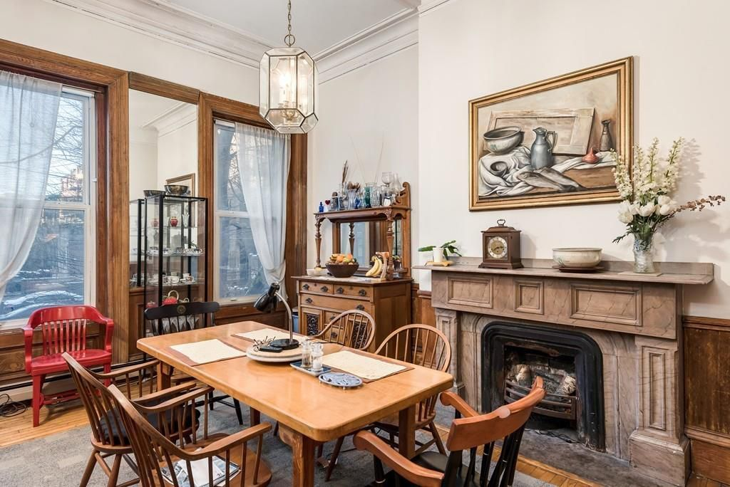 A small dining room with a table and chairs next to a large marble fireplace.