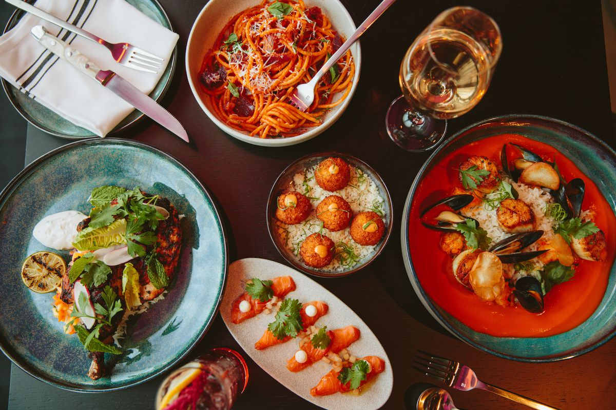 Overhead view of a restaurant table full of food, including a spaghetti dish, a seafood dish, and more