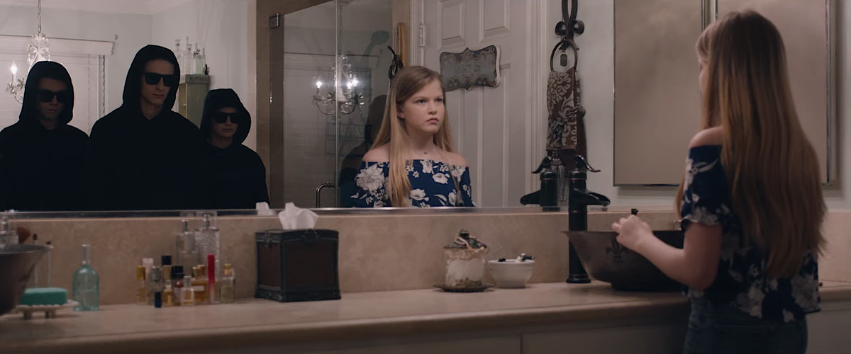 Three ominous teenagers in dark hoodies and sunglasses stand behind a young blonde girl in the reflection of her bathroom mirror in Let Us In