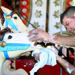 Evencio Gutierrez washed the carousel in preparation for the Utah State Fair at the Utah State Fairpark in Salt Lake City on Wednesday, Sept. 4, 2013. The fair runs Sept. 5-15.