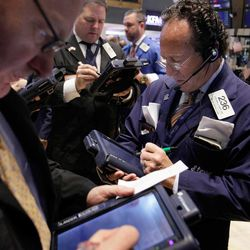 Steven Kaplan, right, works with fellow traders on the floor of the New York Stock Exchange, Monday, April 16, 2012, in New York. The Dow Jones industrial average rose but other stock indexes fell early Monday as a strong report on retail sales didn't dispel worries about the economy.