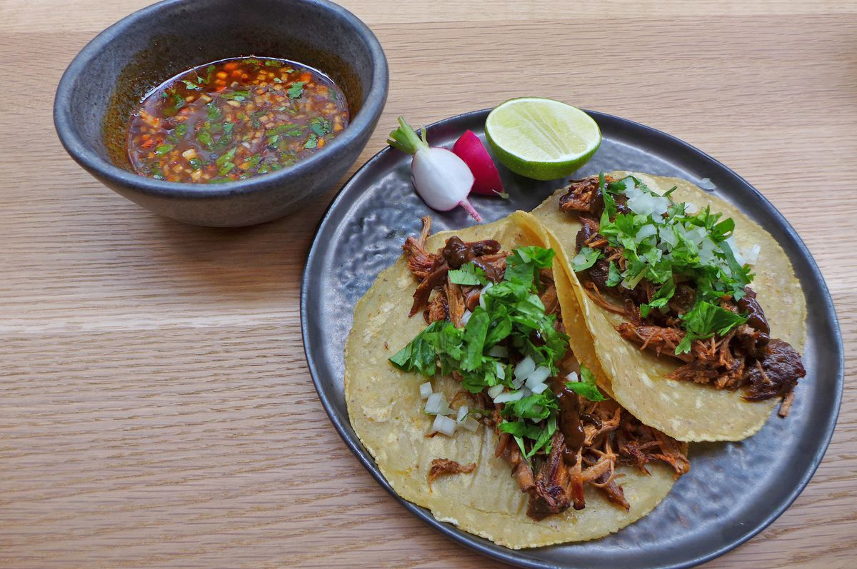 A pair of meat stuffed tacos with dark red soup on the side.