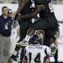 Chattanooga quarterback Jacob Huesman (14) watches South Florida linebacker Sam Barrington (36) and Todd Chandler (95) celebrate a sack during the third quarter of an NCAA college football game Saturday, Sept. 1, 2012, in Tampa, Fla.