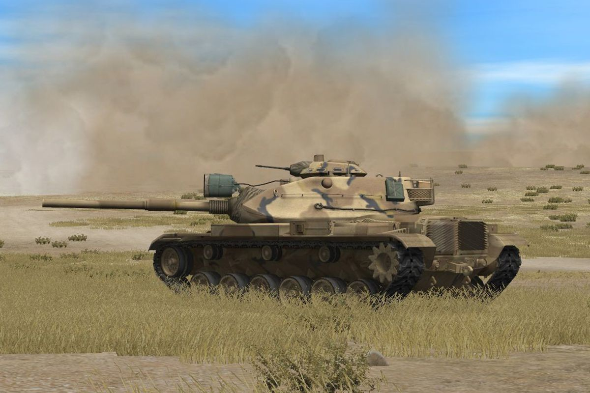 A tank stands on a grassy field, a roadway and a giant cloud of dust in the background.