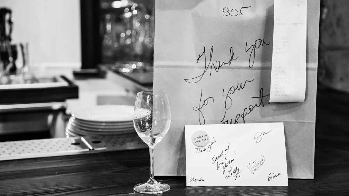 """A brown paper bag sits on a bar with a half-empty wine glass in front of it. Written in Sharpie on the bag is a message reading """"Thank you for your support."""""""