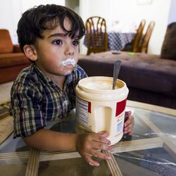 Zain Bilal, 3, takes a break from eating spoonfuls of sugar at his home in Millcreek on Tuesday, Sept. 8, 2015.