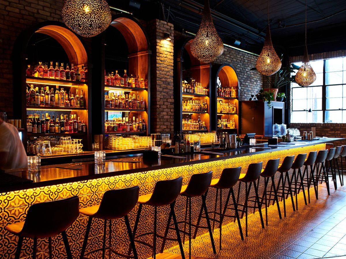Two Wrongs' bar is lit beneath the bartop and behind the built-in shelves, which are carved into the bar's original brick walls