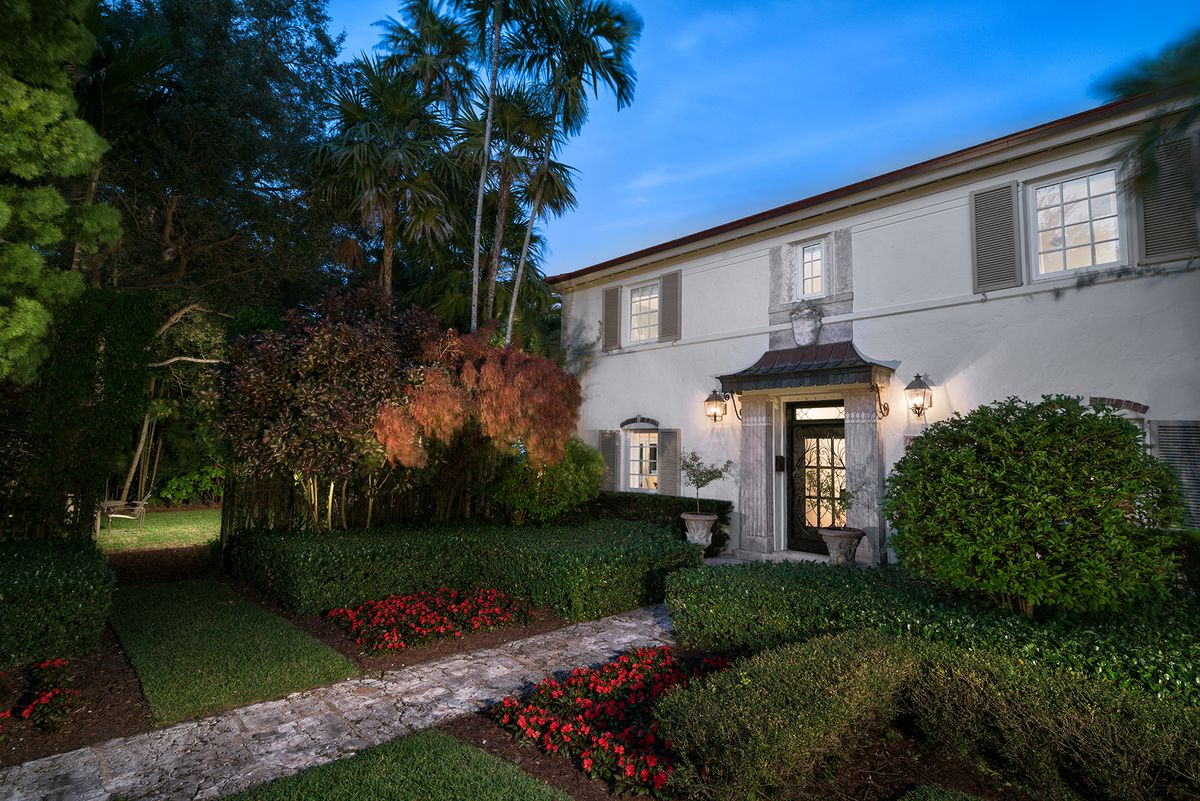 The Coral Gables home of Maria Elena Salinas, a historic white home with lush grounds