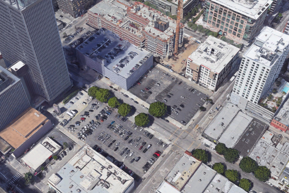 An aerial view of various parking lots and the tops of buildings and skyscrapers.
