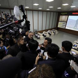 Paek Chang Ho, center, head of the General Launch Command Center, briefs journalists inside the center on the Kwangmyongsong-3 satellite that is expected to be launched in the coming days in Pyongyang, North Korea, Wednesday, April 11, 2012. Engineers are pumping fuel into a rocket that is set to carry the satellite into space, officials at the North Korean space agency's central command center said Wednesday, showing reporters a live feed of the west coast launch pad.