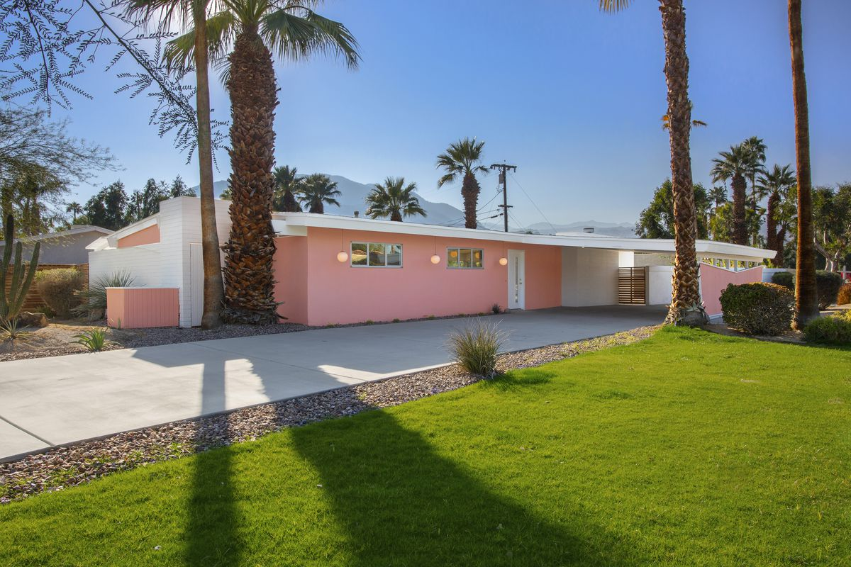 A ranch style house is pink with white accent trim. The house has a long driveway, green grass, and palm trees around it.