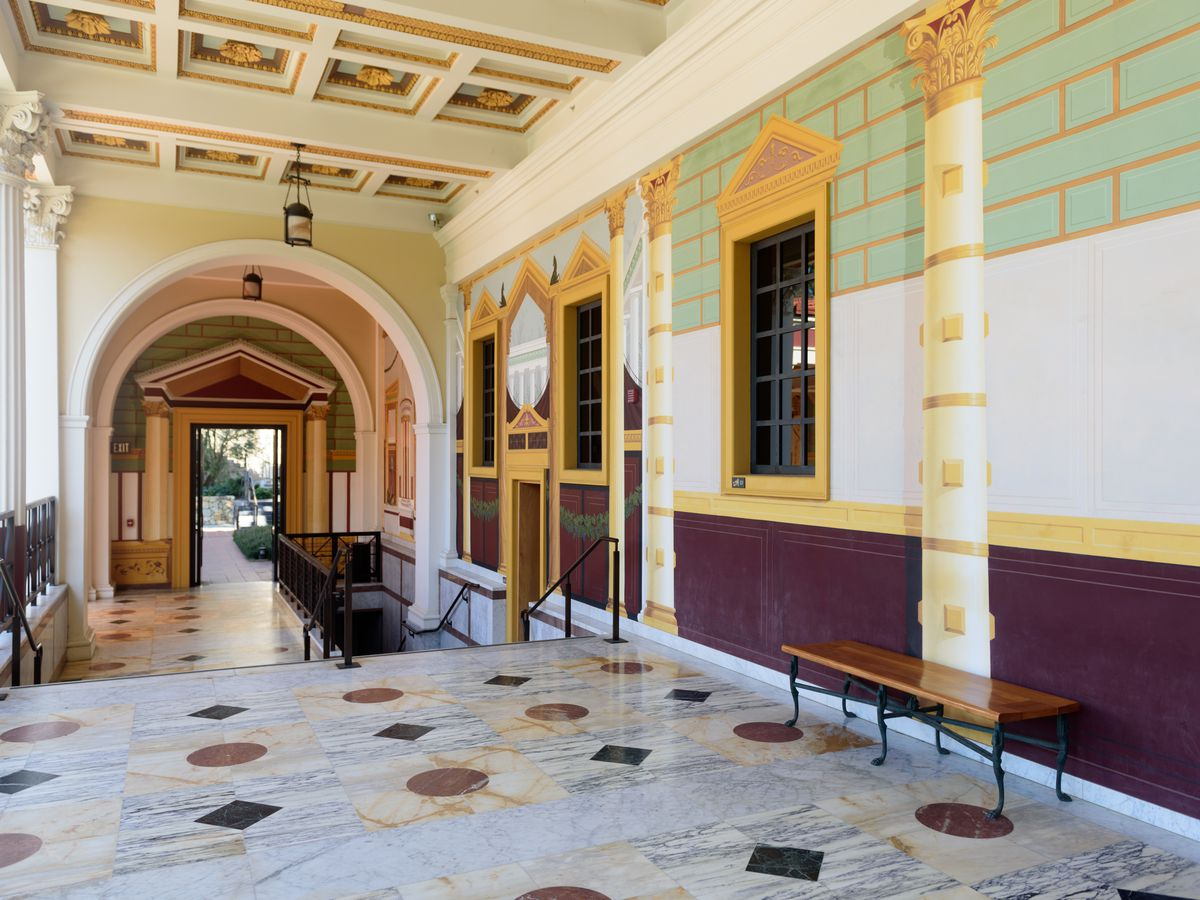 The interior of the Getty villa in California. The floor has white, brown, and black patterned tiles. The walls are green and white. There are domed open doorways.