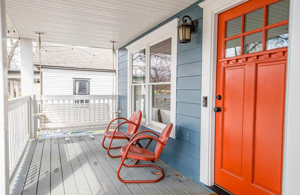 A porch with a white swing and two orange chairs that match the front door of a bungalow.